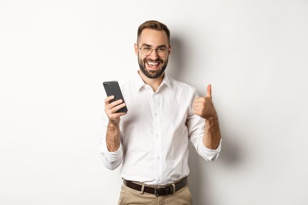 Tevreden zaken man duimen opdagen na het gebruik van mobiele telefoon, blij staan.