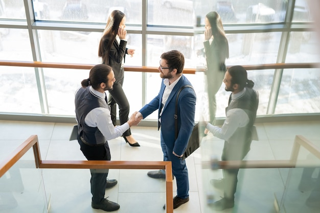 Tevreden zakenlieden die handdruk maken in gang van bureaucentrum, zij bouwen nieuw vennootschap op