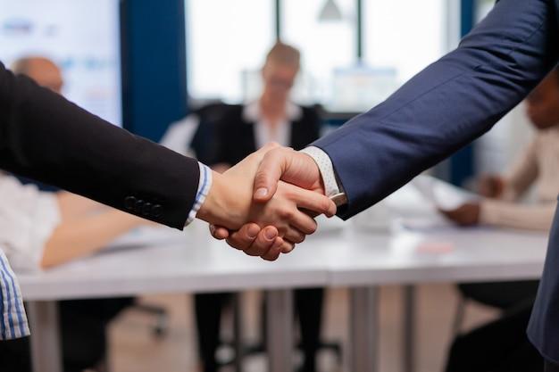 Tevreden zakenman bedrijf werkgever dragen pak handdruk nieuwe werknemer ingehuurd bij sollicitatiegesprek, man hr manager in dienst succesvolle kandidaat schudden hand op zakelijke bijeenkomst, plaatsing concept