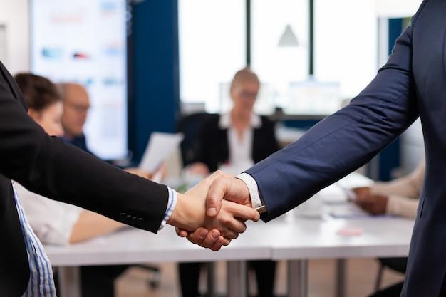 Tevreden zakenman bedrijf werkgever dragen pak handdruk nieuwe werknemer
