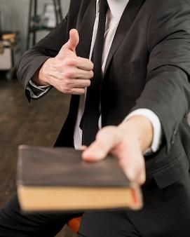 Tevreden zakenman die boek geeft dat duim toont