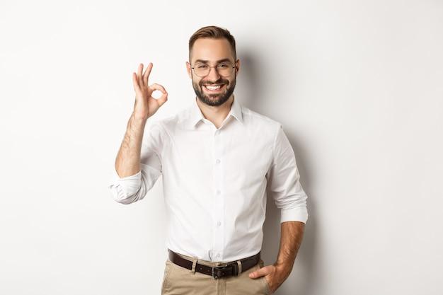 Tevreden zakenman die en ok teken glimlacht toont, keurt goed en houdt van iets goeds, status