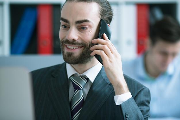 Tevreden zakenman die op de telefoon in het bureau spreekt