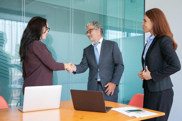Tevreden zakenmensen geven elkaar de hand en begroeten elkaar