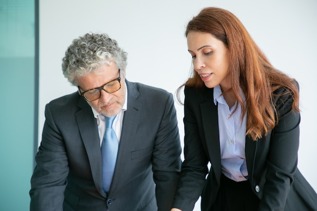 Tevreden zakenmensen kijken naar iets en staan samen
