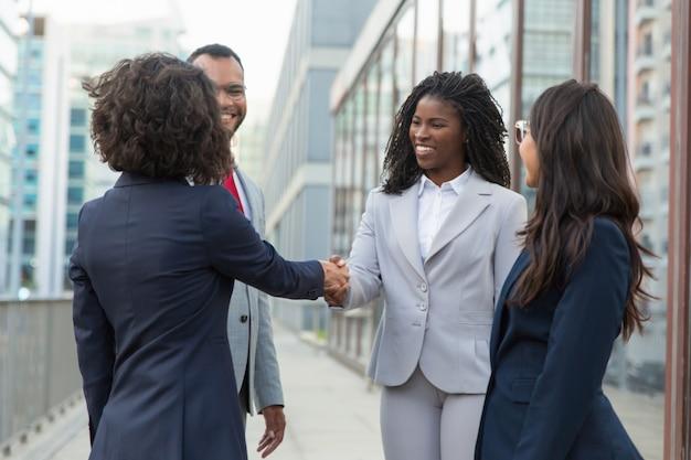 Tevreden zakenpartners die succesvolle vergadering beëindigen
