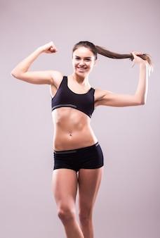 Tevreden zelfverzekerde actieve gezonde vrouw in sportkleding met handen op de heupen