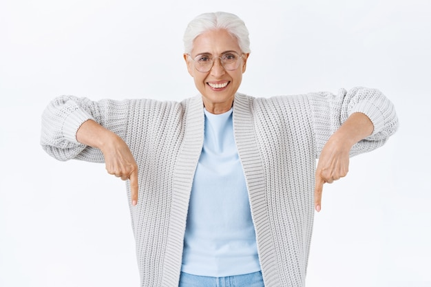 Tevreden, zelfverzekerde, blije, glimlachende gelukkige senior vrouw met grijs haar, in een bril, naar beneden wijzend om de aandacht te trekken geweldige promo-verkoop, haar enthousiasme tonen, advertentie aanbevelen, klik op banner