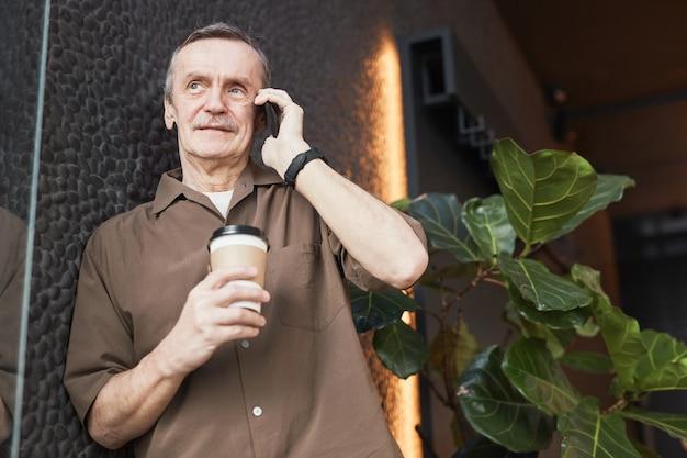 Tevreden zelfverzekerde senior blanke zakenman met snor die aan een stenen muur staat en koffie drinkt terwijl hij het project telefonisch bespreekt