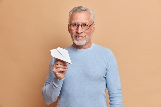 Tevreden zelfverzekerde volwassen grijsharige man met glimlach houdt handgeschept papieren vliegtuigje zeker weten in een succesvolle toekomst draagt een bril en blauwe trui geïsoleerd over bruine muur