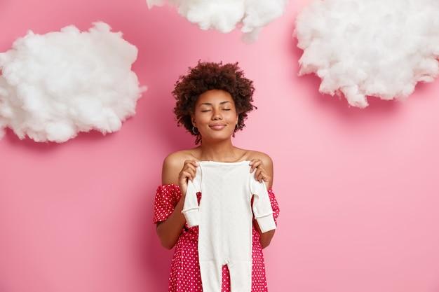 Tevreden zwangere vrouw houdt babypakje over buik, bereidt kinderkleding voor, staat met gesloten ogen, maakt zich klaar voor kraamkliniek, poseert tegen roze muur met wolken. moederschap concept