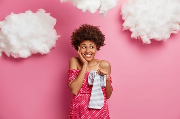 Tevreden zwangere vrouw met afro haar houdt hand op wangen houdt baby romper glimlacht aangenaam draagt jurk heeft grote buik poses
