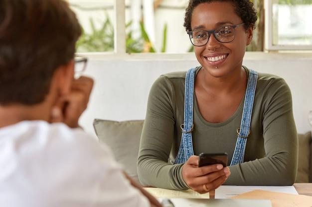 Tevreden zwarte lachende jonge vrouw in glazen, draagt piercing, houdt moderne mobiele telefoon, heeft een aangenaam gesprek samen met een onherkenbare man die achterover leunt, samenwerking bespreken