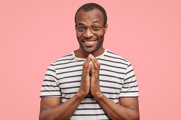 Tevreden zwarte man met tevreden uitdrukking maakt biddend gebaar, glimlacht positief