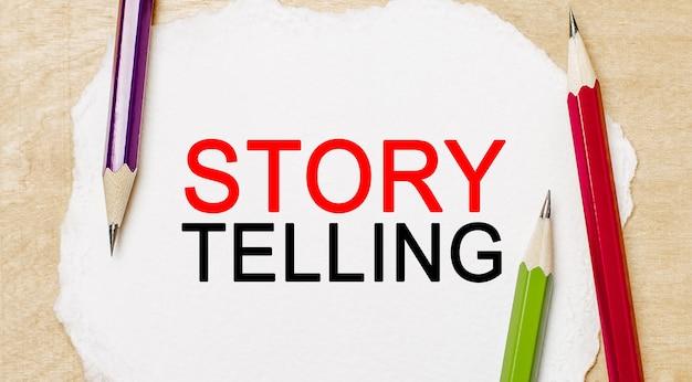 Text storytelling op een witte blocnote met potloden op een houten achtergrond. bedrijfsconcept