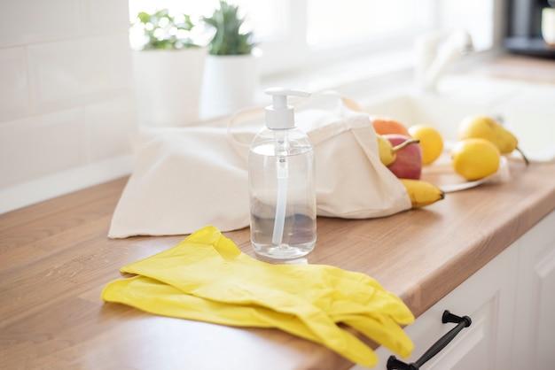 Textiel draagtas gevuld met vers fruit op het aanrecht, in de buurt van de gootsteen, klaar om te worden gewassen. wasmiddel en beschermende handschoenen. coronavirus preventie. hygiëne om het coronavirus te stoppen
