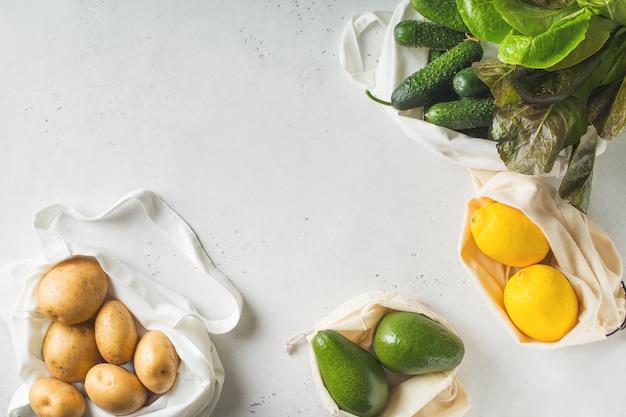 Textiel ecologische boodschappentassen met fruit en groenten op witte achtergrond