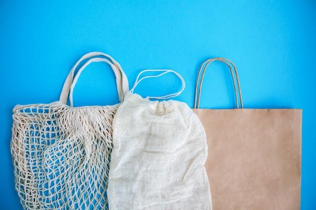Textiel en papieren eco-tassen op blauw.