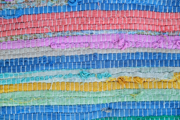 Textiel veelkleurige textuur achtergrond. close-up van vloerkleed geweven van gekleurde draden