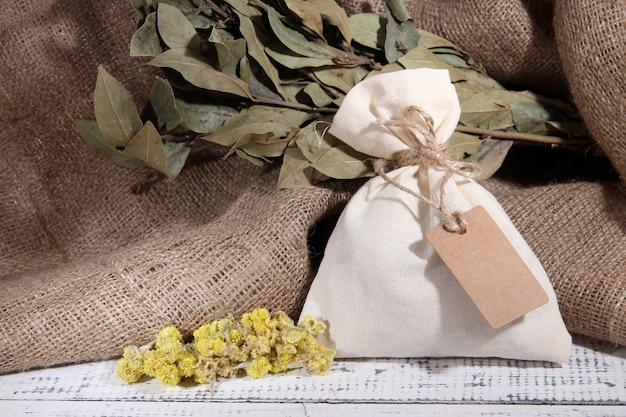 Textiel zakje zakje met gedroogde bloemen op houten tafel, op jute achtergrond