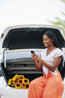 Texting vrouw zit in de kofferbak van de auto
