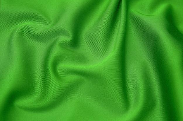Textuur, achtergrond, patroon. textuur van groene zijdestof. mooie smaragdgroene zachte zijden stof.