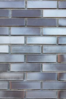 Textuur achtergrond van een zilveren muur gemaakt van keramiek geconfronteerd met donker grijsbruine bakstenen.