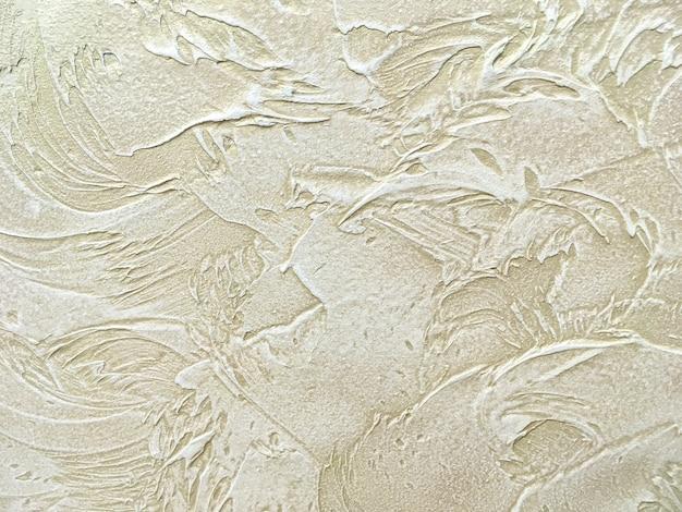 Textuur decoratief beige pleister die de oude schilmuur imiteren.