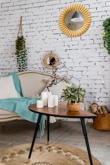 Textuur kussens op beige sofa, mint deken. kleine tafel met kaarsen. stijlvolle scandinavische interieur van woonkamer met sofa, kussens, elegante persoonlijke accessoires en planten op bakstenen muur.