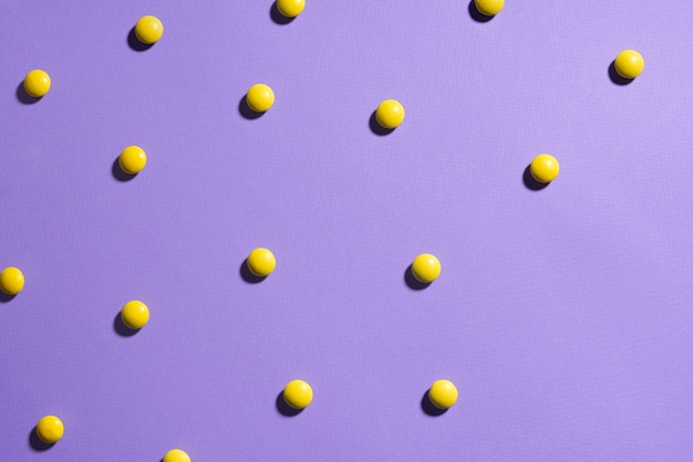 Textuur paarse achtergrond met gele chocolade snoepjes