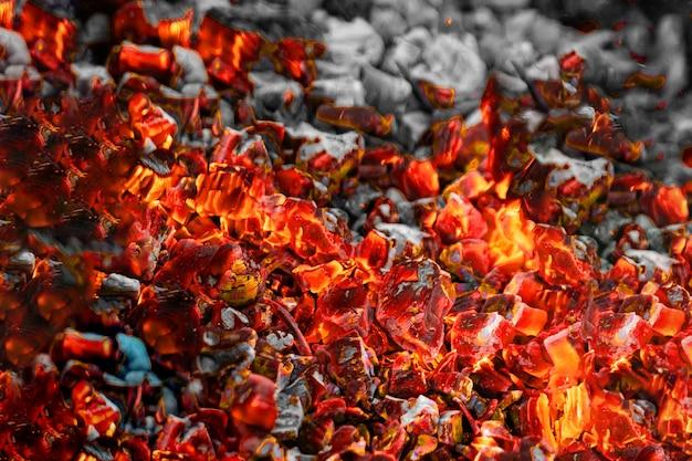 Textuur roodgloeiende steenkolen, selectieve nadruk. barbecue donkere achtergrond