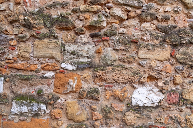 Textuur van antieke metselwerkmuur. het patroon van een stenen muur. (veelkleurige stenen)