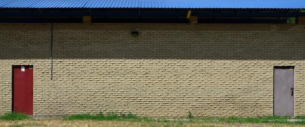 Textuur van bakstenen muur van hulpstenen onder helder zonlicht met twee metaaldeuren