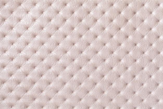 Textuur van beige leer stof achtergrond met capitone patroon. crème textiel in chesterfield-stijl.