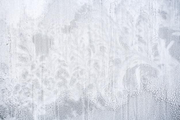 Textuur van bevroren sneeuw op vensterglas in vorm van fantastische installaties.