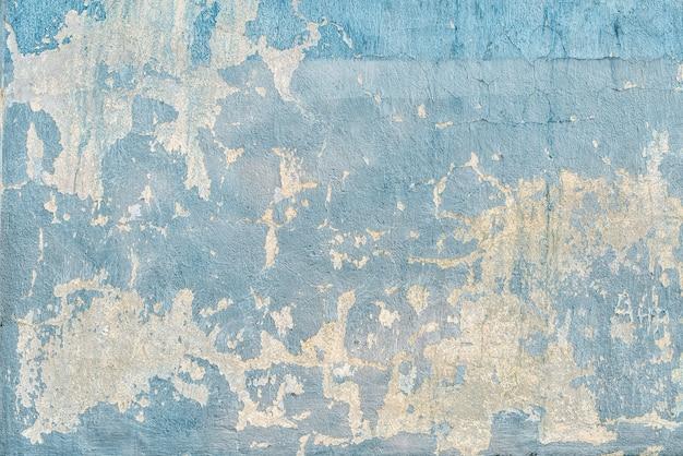 Textuur van blauwe gebarsten muur in krassen