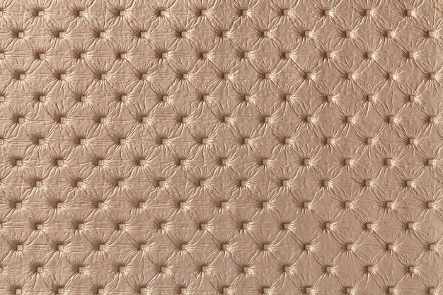 Textuur van bruin leer stof achtergrond met capitone patroon, macro. bronzen textiel in chesterfield-stijl.