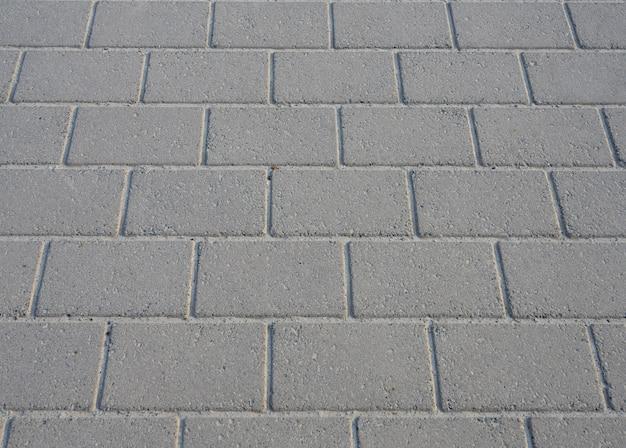 Textuur van de concrete vloer van de gangbaksteen op de achtergrond van de perspectiefclose-up.