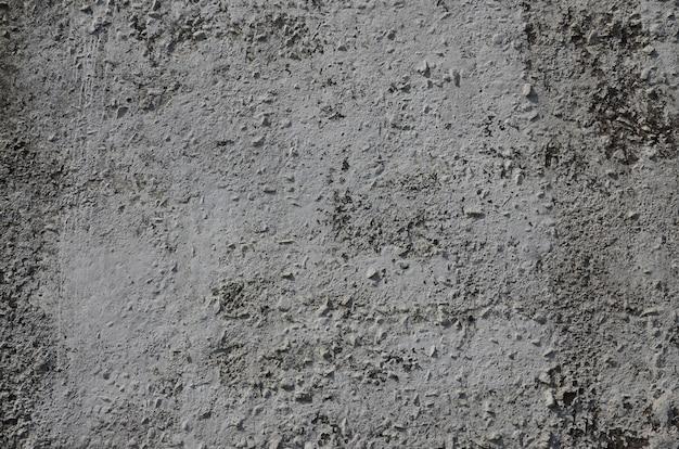 Textuur van de oude in reliëf gemaakte concrete muur in grijze kleur. achtergrond van een concreet product