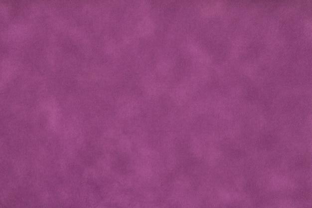 Textuur van donker paars oud papier, verfrommelde achtergrond. vintage lila grunge oppervlakte achtergrond. structuur van ambachtelijk perkamentkarton.