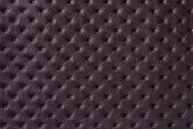 Textuur van donkerbruine leerachtergrond met capitonepatroon, macro. paars textiel in retro chesterfield-stijl.
