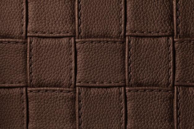 Textuur van donkerbruine leerachtergrond met vierkant patroon en steek, macro.