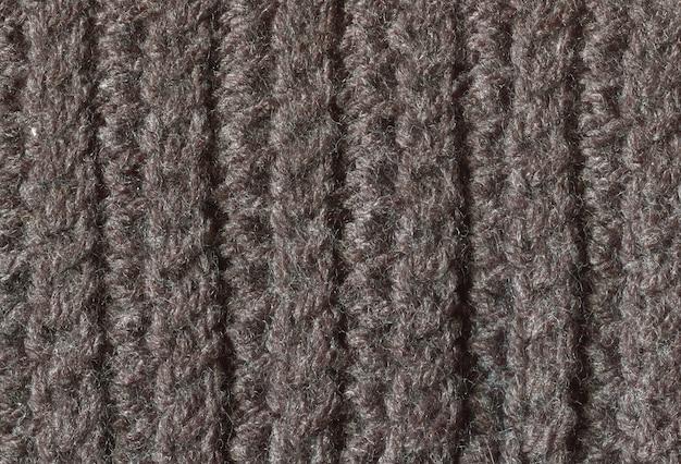Textuur van donkere gebreide stoffenachtergrond