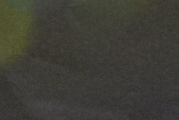 Textuur van donkere stof met gele vlek