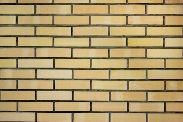 Textuur van een gele bakstenen muur achtergrond op het platteland, ruwe blokken steen, baksteen metselwerk horizontale kleur technologie architectuur behang. bakstenen gele muur.