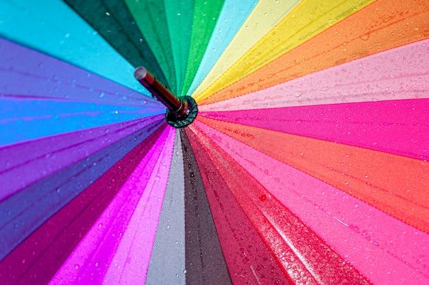 Textuur van een heldere regenboogparaplu met dalingen