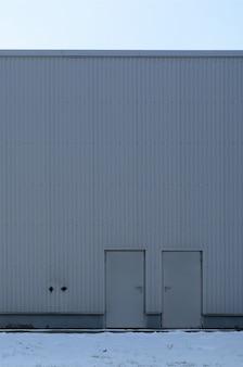Textuur van een hoge metaalmuur van een industrieel gebouw zonder vensters