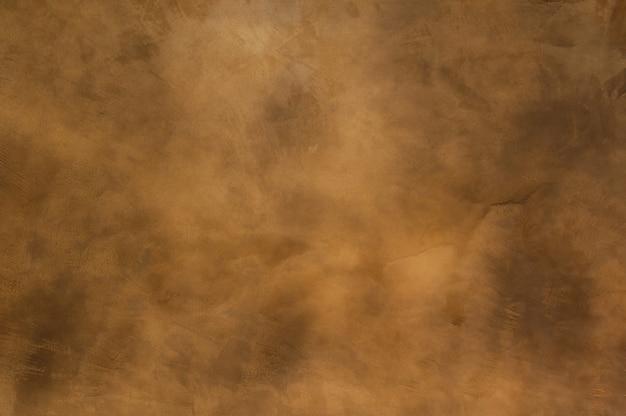Textuur van een oranje bruin beton als achtergrond, bruine grungy muur