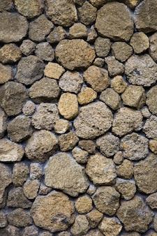 Textuur van een oude stenen muur van ongelijke verschillende oude stenen van verschillende vormen