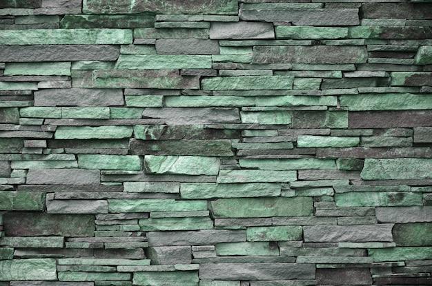 Textuur van een stenen muur van lange en ruwe stenen van verschillende grootten en tonen